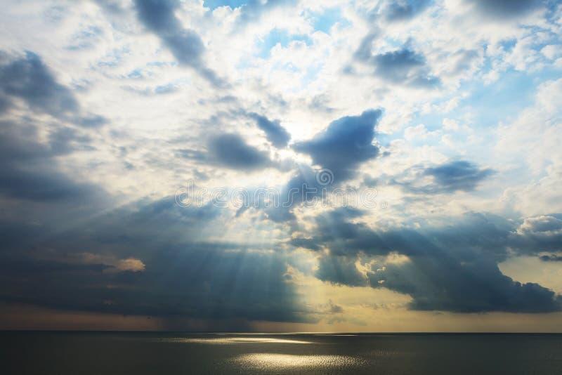 Vista sul mare nuvolosa dopo la tempesta che vede i raggi di sole naturali al tramonto immagini stock libere da diritti
