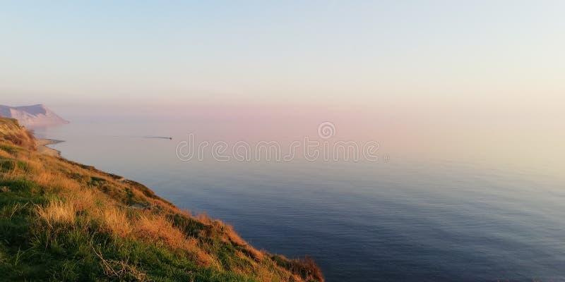 Vista sul mare Rosa splendido e tramonto lilla sopra l'estensione calma del mare immagine stock libera da diritti