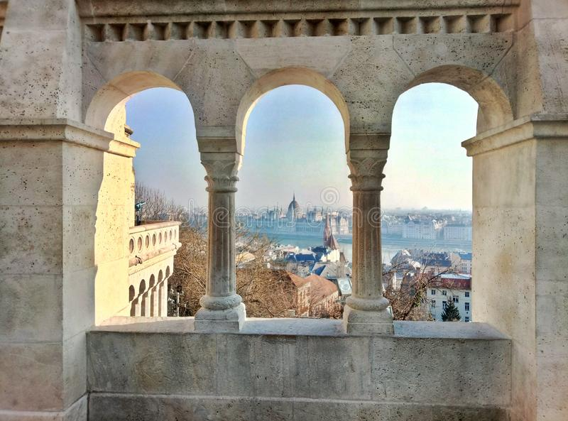 Vista sul Parlamento gotico di Budapest attraverso le colonne del bastione del pescatore immagine stock