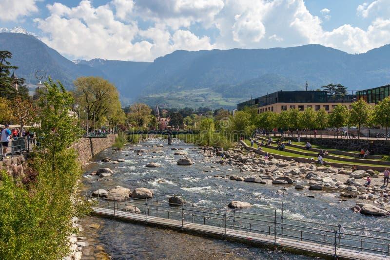 Vista sul passante del fiume con passeggiata, vegetazione ed intorno alle costruzioni in Meran Provincia Bolzano, Tirolo del sud, immagini stock libere da diritti