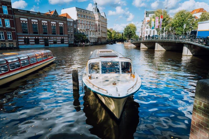 Vista sul ponte attraverso il canale del fiume con la barca nell'immagine anteriore e tipica dei canali a Amsterdam fotografia stock