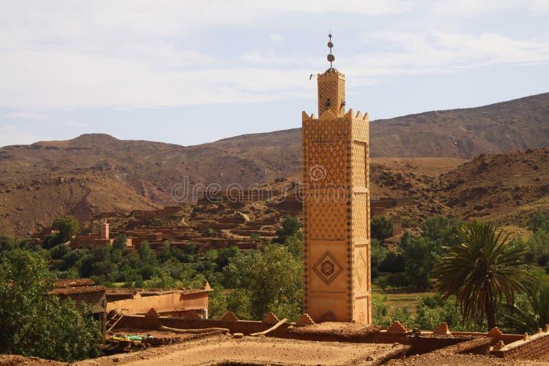 Vista sul villaggio arabo di vecchio berbero con le case con mattoni a vista dell'argilla in valle con pianta ed il minareto immagini stock