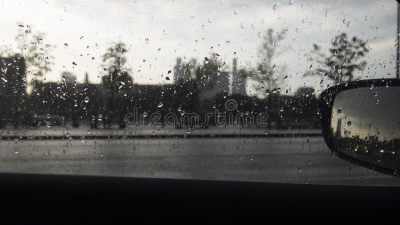 Vista sulla città di Mosca Gocce dalla pioggia sul vetro di un'automobile, il paesaggio urbano nel defocusing Riflessione dei far fotografia stock