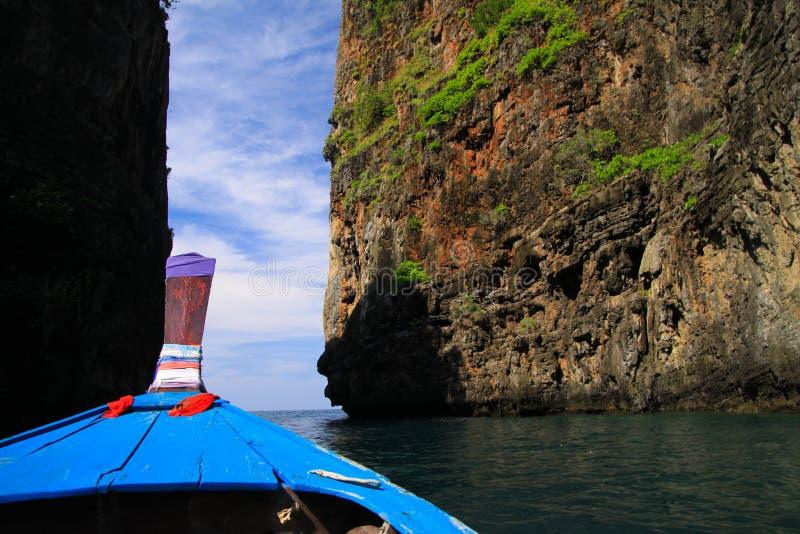 Vista sulla prua di legno decorata blu della barca e del passaggio del longtail fra le pareti della roccia da entrambi i lati sot fotografia stock libera da diritti