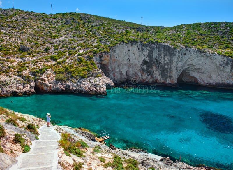 Vista sulle caverne blu della baia della spiaggia della roccia di Zacinto, ragazza graziosa che considera la baia dell'acqua blu  fotografia stock