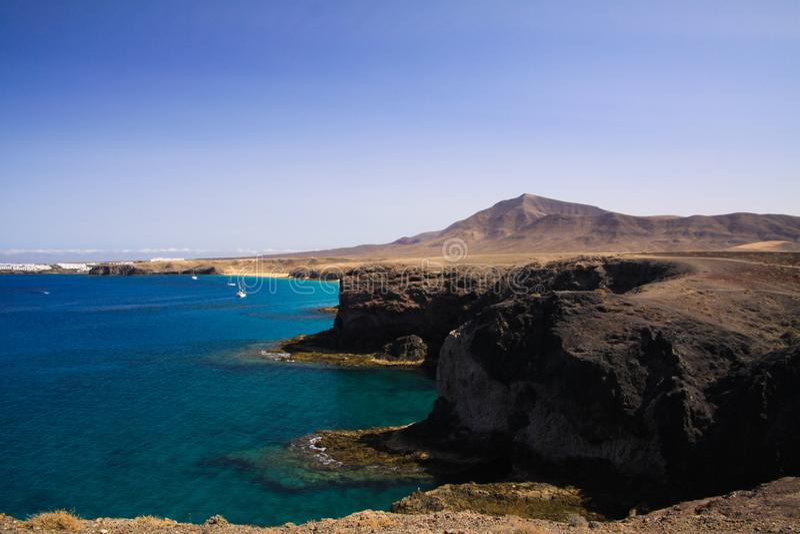 Vista sulle scogliere irregolari ripide della costa di Punta del Papagayo, BLANCA di Playa - Lanzarote fotografie stock