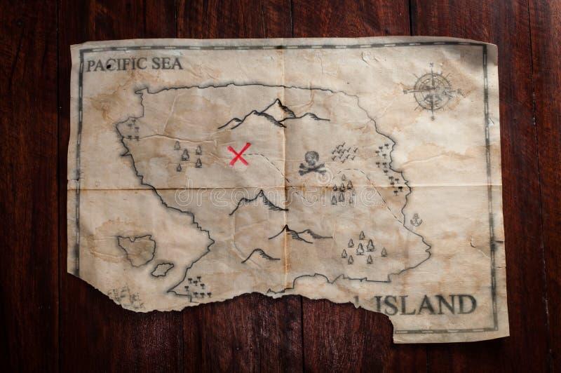 A vista superior à falsificação do vintage amarrotou o mapa do tesouro na tabela de madeira Mapa feito a mão do pirata falsificad imagens de stock