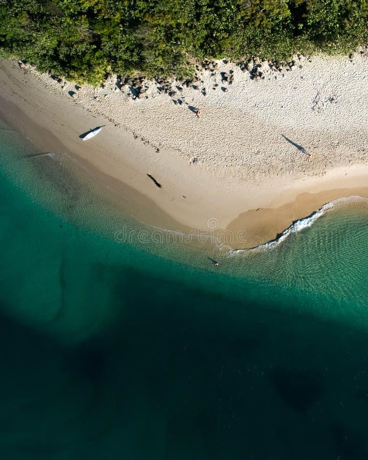 Vista superior aérea da praia com areia branca, os guarda-chuvas bonitos e água tropical de turquesa morna foto de stock royalty free