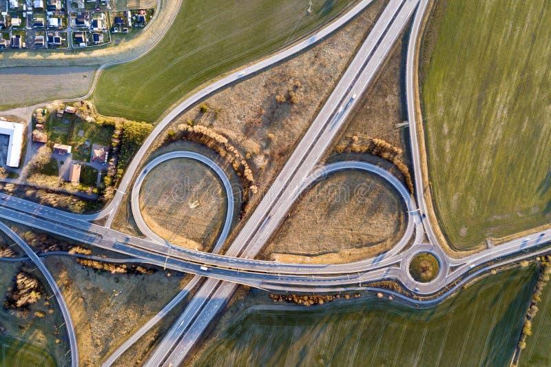 Vista superior aérea de la intersección moderna del camino de la carretera, tejados de la casa en fondo del campo del verde de la foto de archivo