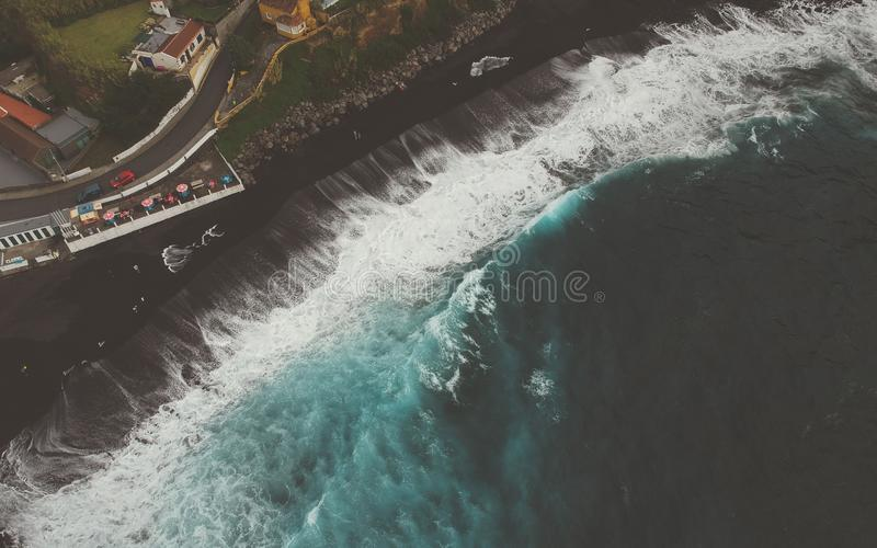 Vista superior aérea de las ondas del mar que golpean una playa con la arena volcánica negra con la agua de mar de la turquesa imágenes de archivo libres de regalías