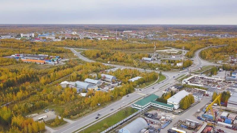 Vista superior aérea de los árboles hermosos del otoño y el área industrial de la ciudad con los edificios clip Muchos coches móv fotos de archivo libres de regalías