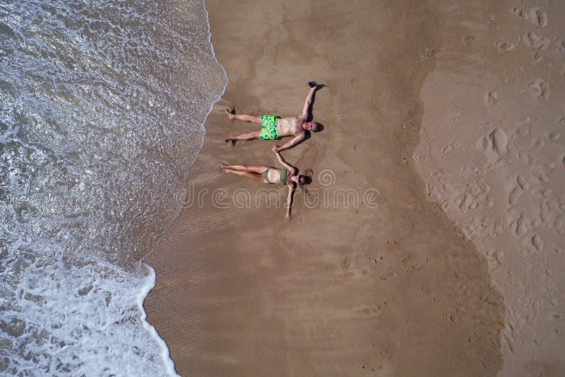 Vista superior aérea de los pares que ponen en la playa arenosa fotografía de archivo libre de regalías