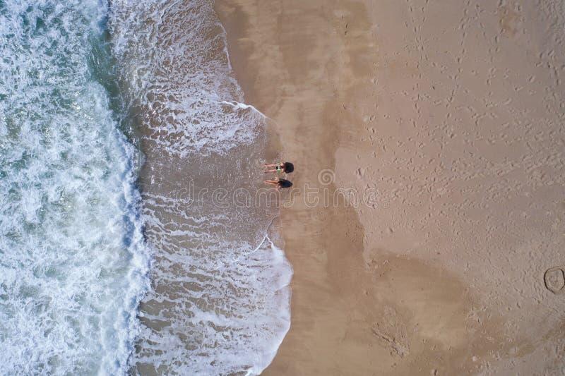 Vista superior aérea de los pares que ponen en la playa arenosa imágenes de archivo libres de regalías