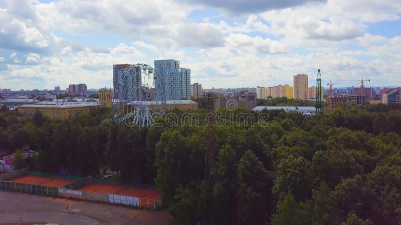 Vista superior aérea del parque de atracciones para los niños en un día de verano Noria en el Central Park de la ciudad aéreo imagen de archivo libre de regalías