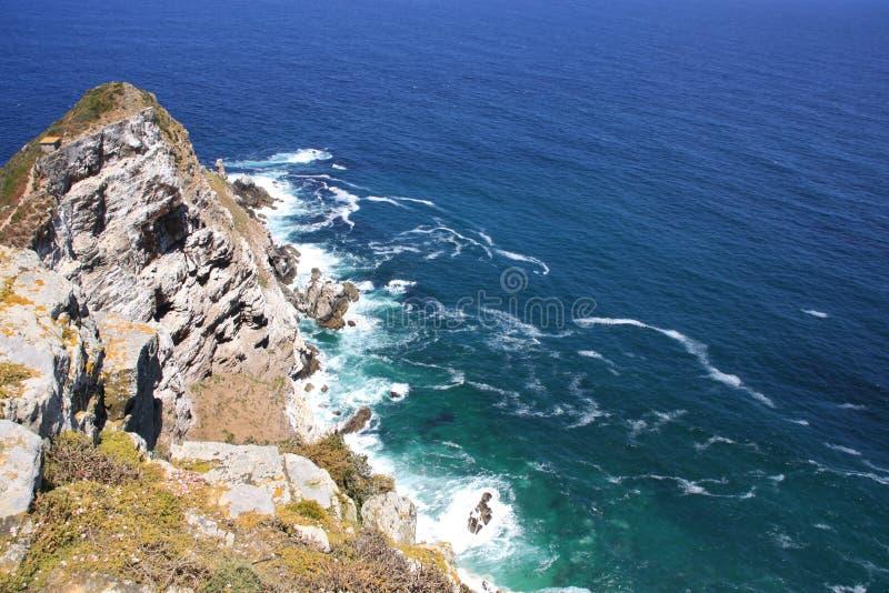 A vista superior aérea do mar acena a batida cercado pelo ponto das rochas imagem de stock