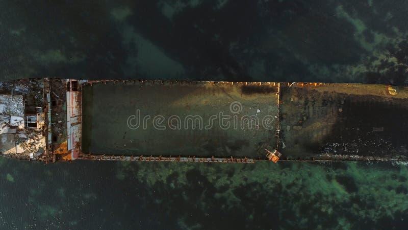 Vista superior aérea para o navio destruído ao longo da costa rochosa na água azul tiro Barco afundado velho perto da costa de ma foto de stock royalty free
