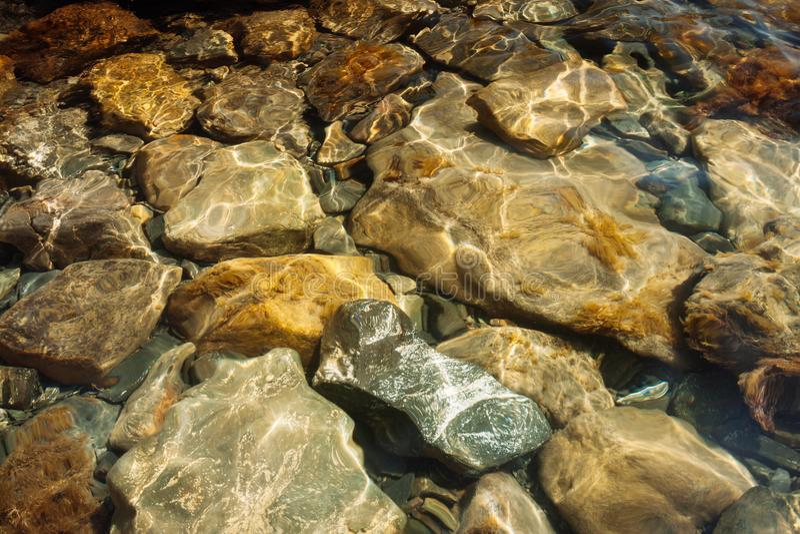 Vista superior através da água clara em pedras bonitas do mar de tamanhos diferentes imagens de stock royalty free