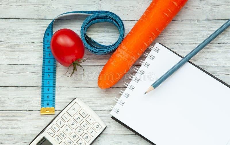 Vista superior, bloco de notas e tomate suculento com cenouras, conceito do emagrecimento e comer saudável imagens de stock