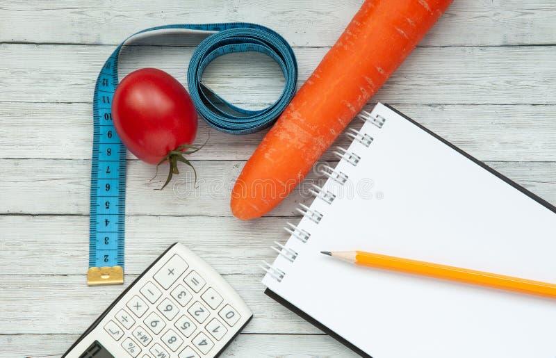 Vista superior, bloco de notas e tomate suculento com cenouras, conceito do emagrecimento e comer saudável imagens de stock royalty free