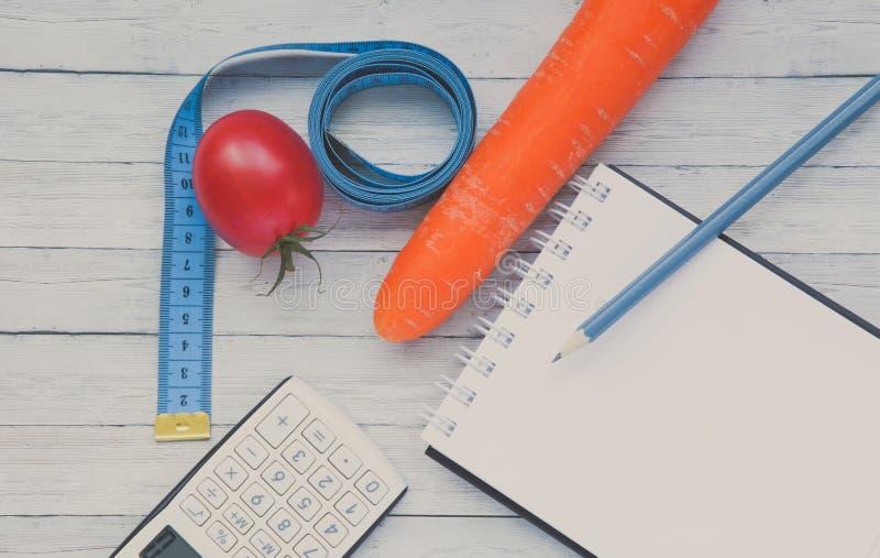 Vista superior, bloco de notas e tomate suculento com cenouras, conceito do emagrecimento e comer saudável fotografia de stock royalty free