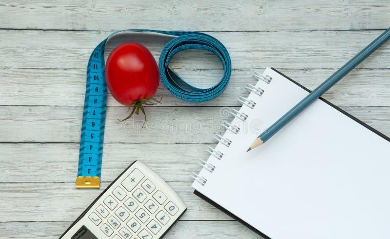 Vista superior, bloco de notas e tomate suculento com fita de medição, conceito do emagrecimento e comer saudável fotos de stock royalty free