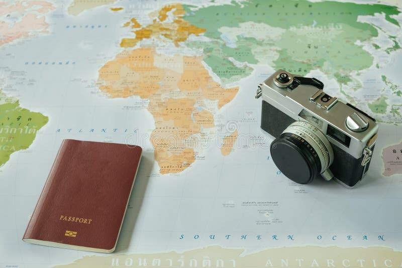Vista superior a câmera retro e o passaporte colocaram sobre o mapa do mundo a fotos de stock