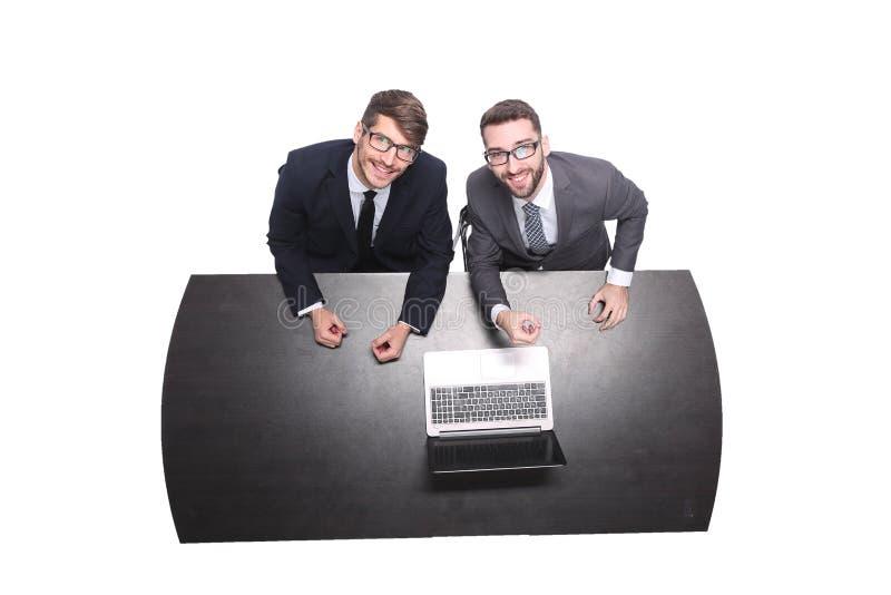 Vista superior colegas de sorriso do negócio que sentam-se na frente de um portátil aberto imagem de stock