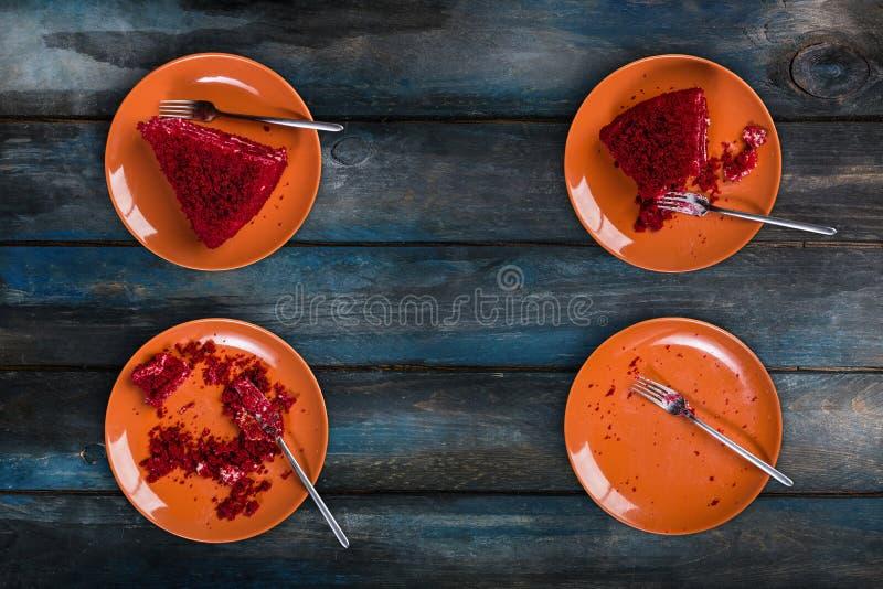Vista superior Comendo o processo de bolo vermelho delicioso de veludo em uma placa cerâmica com uma forquilha em um fundo de mad imagem de stock royalty free