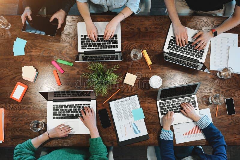 Vista superior da analítica nova do negócio que senta-se na tabela Equipe de Coworking que trabalha junto fotografia de stock