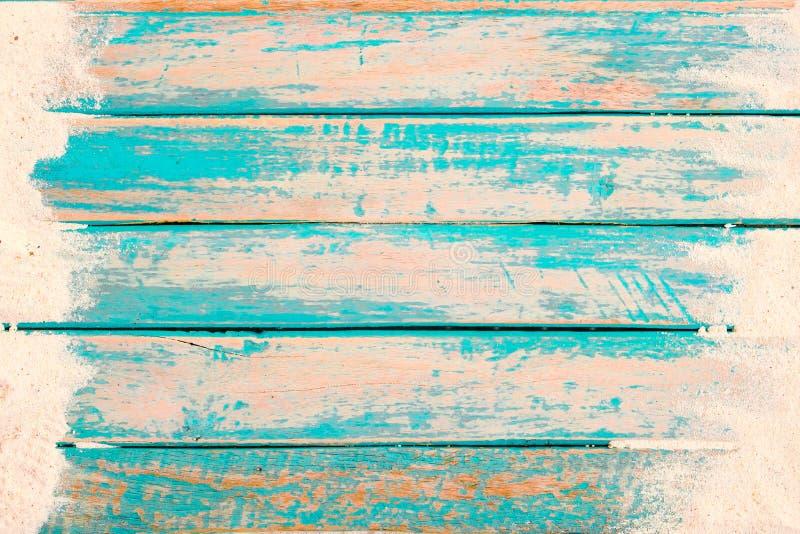Vista superior da areia da praia na prancha de madeira velha no fundo azul da pintura do mar imagens de stock royalty free