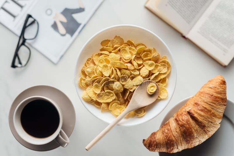 vista superior da bacia de café da manhã do cereal seco com xícara de café e croissant na superfície branca com jornal imagem de stock