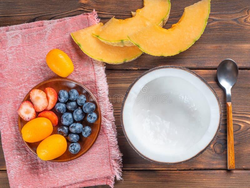 Vista superior da bacia do coco e mirtilos e morangos e melão e kumquat e colher de chá vazios em um fundo de madeira imagens de stock
