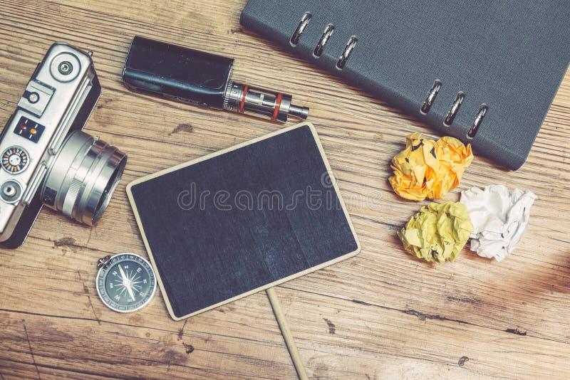 A vista superior da câmera do vintage, amarrota o papel, o cigarro eletrônico e a disposição do livro do planejador no assoalho d foto de stock