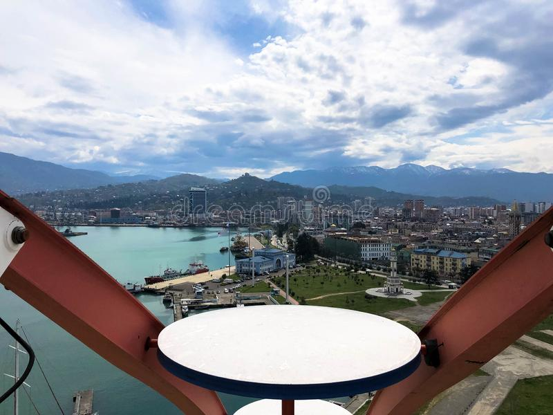 A vista superior da cabine de uma roda de ferris sobre a cidade com casas, as construções, o mar azul e as montanhas altas em um  fotografia de stock royalty free