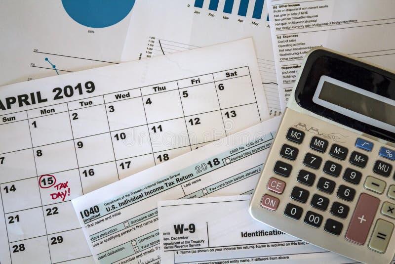 A vista superior da calculadora, dos formulários de imposto, dos gráficos e da folha do calendário com data do imposto marcou fotografia de stock royalty free