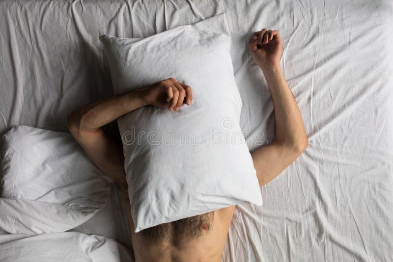 vista superior da cara escondendo do homem descamisado com descanso ao dormir na cama imagens de stock royalty free