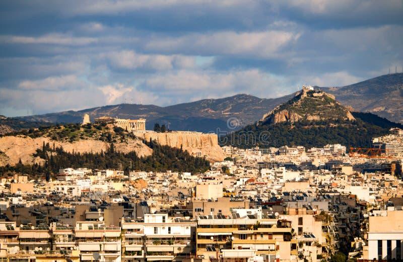 Vista superior da casa, as montanhas, monte da acrópole e do Likavitos e a arquitetura urbana de Atenas em um dia ensolarado fotos de stock