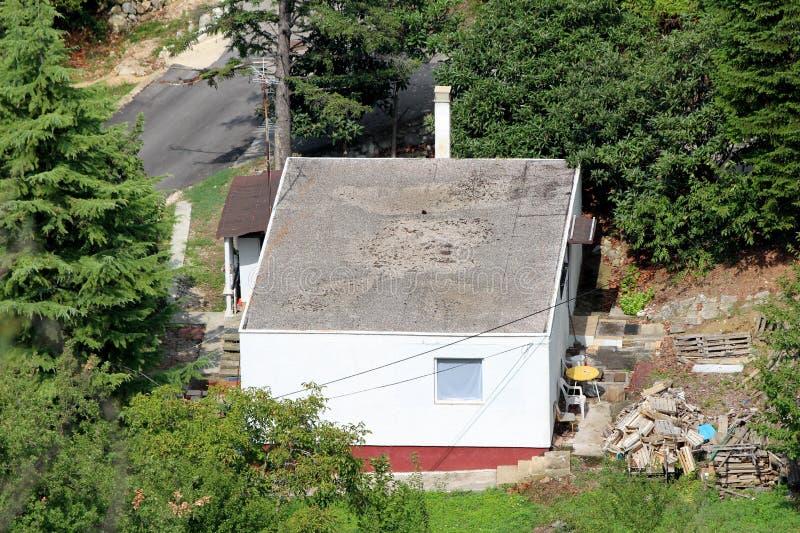 Vista superior da casa pequena da família do rés do chão com telhado liso e material de construção no quintal cercado com florest fotografia de stock royalty free