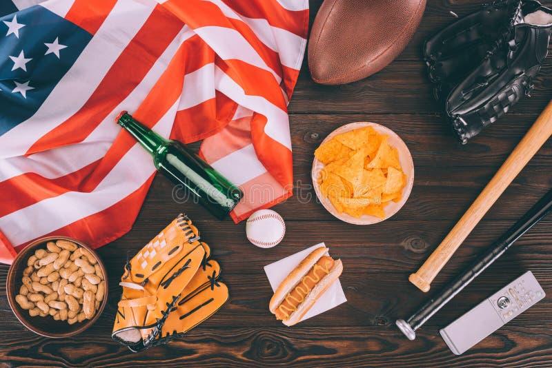 vista superior da comida lixo, da bandeira americana e do equipamento de esporte fotografia de stock