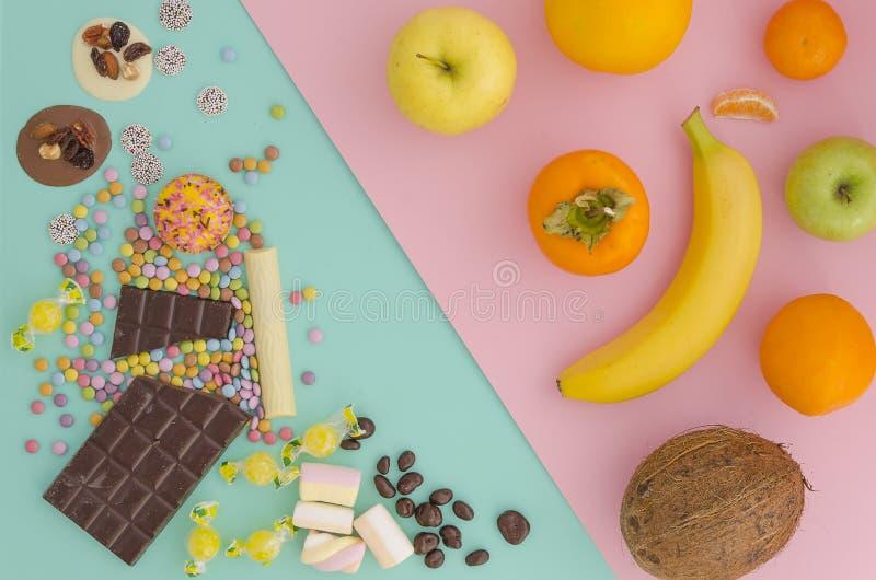 Vista superior da comida lixo sortido, dos doces e do chocolate contra frutos frescos no rosa vibrante e na hortelã do duotone da foto de stock