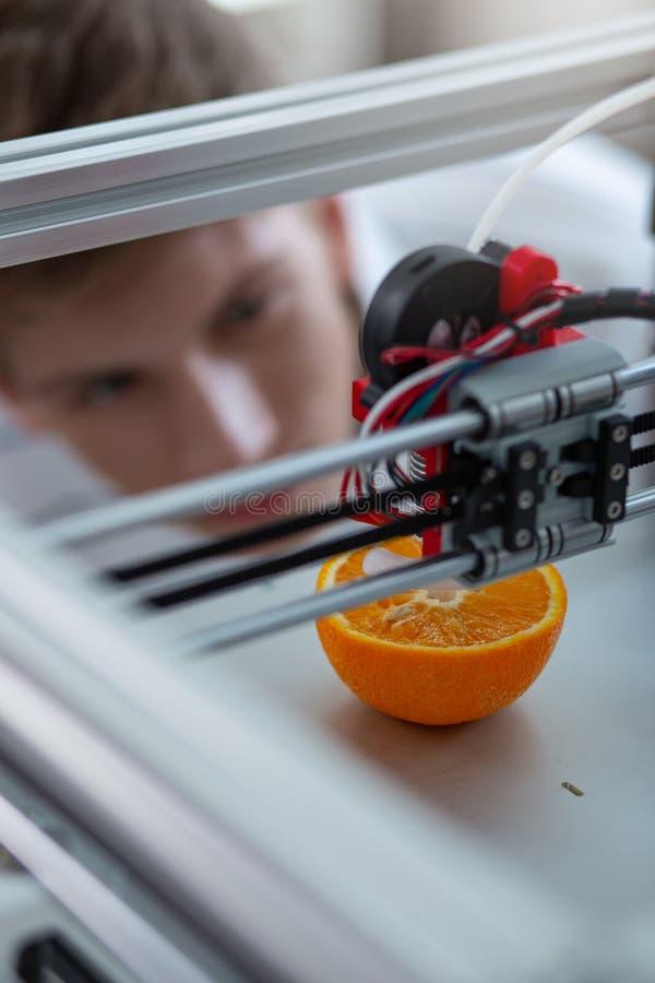 Vista superior da impressora 3D que cria o modelo da laranja fotografia de stock royalty free