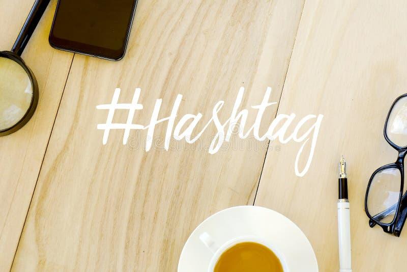 Vista superior da lupa, do telefone celular, de uma xícara de café, da pena e dos vidros no fundo de madeira escrito com #hashtag ilustração do vetor