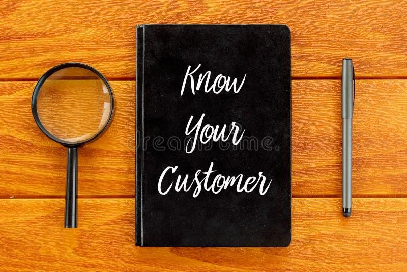 Vista superior da lupa, da pena e do caderno escritos com para conhecer seu cliente no fundo de madeira Conceito do negócio e da  ilustração stock