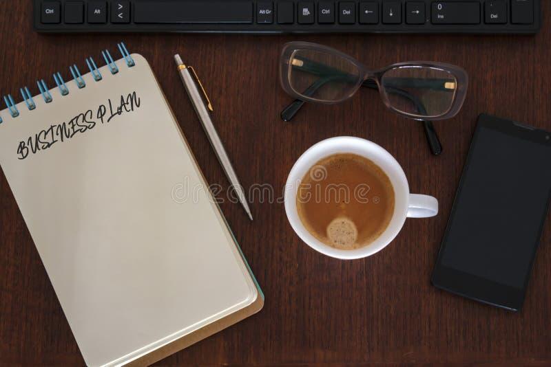 Vista superior da mesa de escritório com acessórios e caderno do escritório com o plano de negócios redigido Conceito da estratég fotografia de stock royalty free
