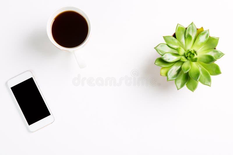 Vista superior da mesa de escritório vazia Planta verde em um potenciômetro com xícara de café e telefone celular moderno e no fu foto de stock