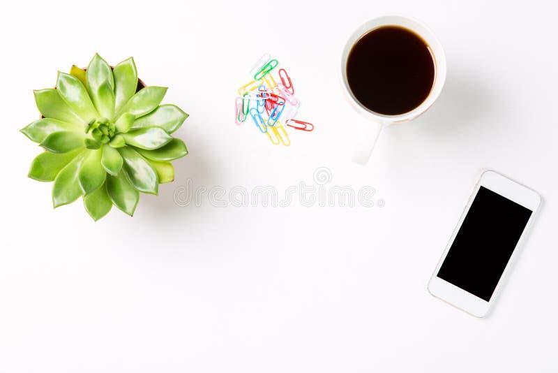 Vista superior da mesa de escritório vazia Planta verde em um potenciômetro com xícara de café, telefone celular moderno e clipes fotos de stock royalty free