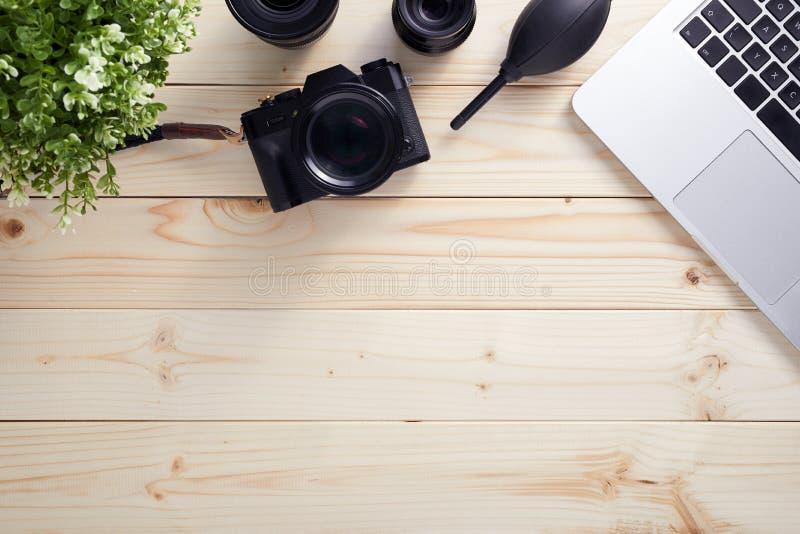 Vista superior da mesa do fotógrafo com latptop, câmera e lentes Tiro colocado liso na mesa de madeira fotos de stock royalty free