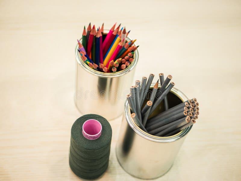 Vista superior da mesa limpa com as latas de lata dos lápis e do carretel da linha imagem de stock royalty free