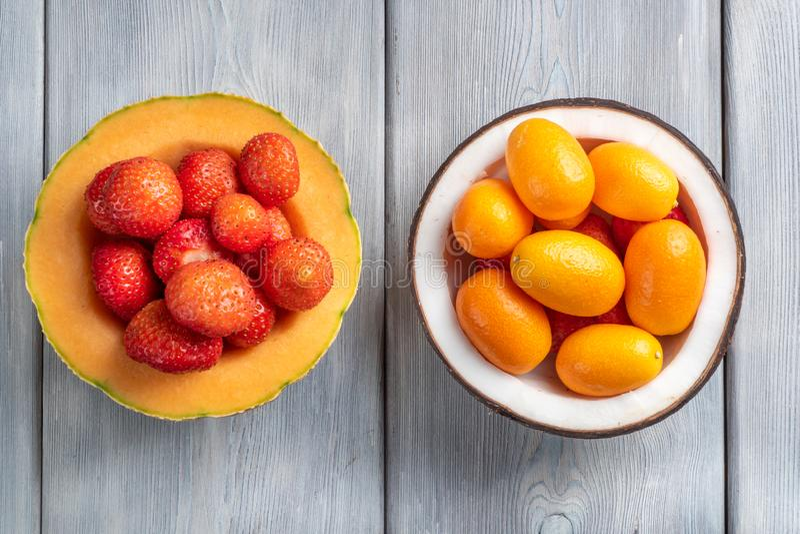 Vista superior da morango no melão e no kumquat na bacia do coco no fundo de madeira branco fotografia de stock