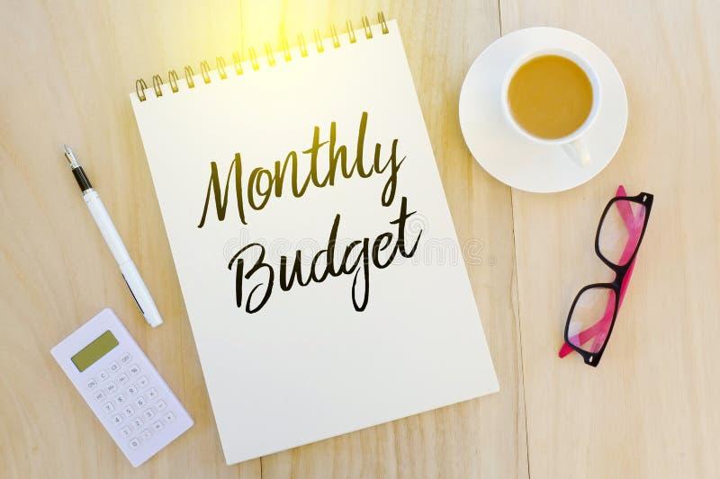 Vista superior da pena, da calculadora, dos óculos de sol, de uma xícara de café e do caderno escritos com orçamento mensal no fu foto de stock royalty free